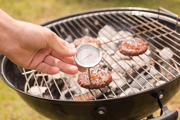 Man using meat thermometer while barbecuing on a sunny day